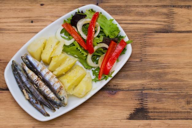 Gebraden sardines met gekookte aardappel en salade op witte plaat op bruin hout