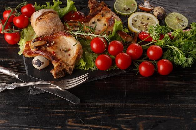 Gebraden varkenskotelet op een zwarte plaat met kruiden, kruiden en tomaten.