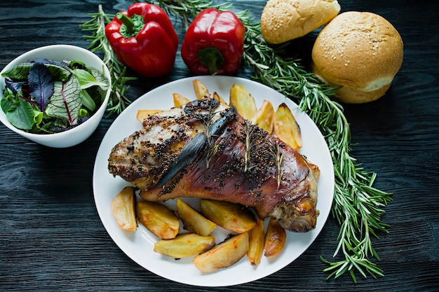 Gebraden varkensvleesgewricht met aardappels die op een witte plaat worden gediend