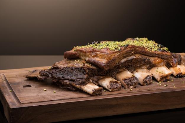 Gebraden vlees met bot op een houten dienblad, donkere achtergrond, geïsoleerd