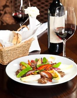 Gebraden vlees met erwten en uien naast rode wijn