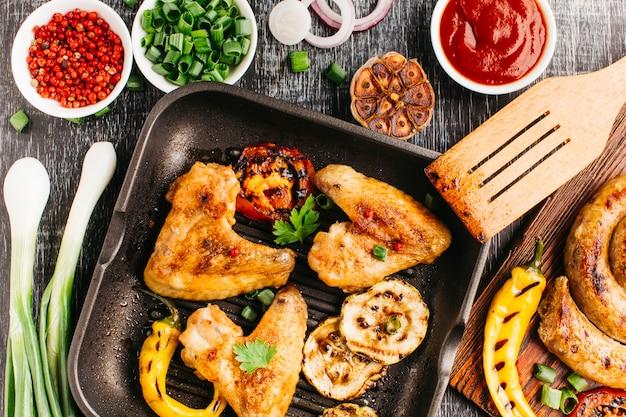 Gebraden vlees met plantaardige en spiraalvormige worst op houten bureau