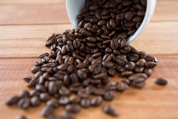 Gebrande koffiebonen die uit de beker morsen