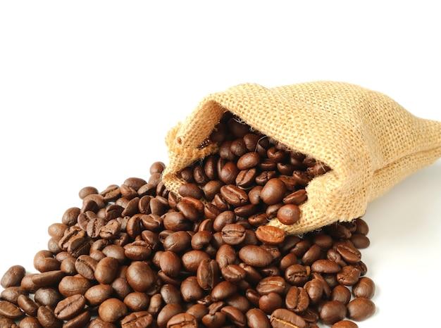 Gebrande koffiebonen die van geïsoleerde jutezak worden verspreid