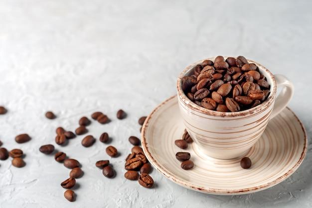 Gebrande koffiebonen in een keramische kop symbolische afbeeldingskopieerruimte