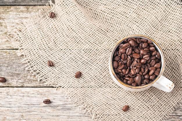 Gebrande koffiebonen in een kopje. bovenaanzicht. ruimte kopiëren