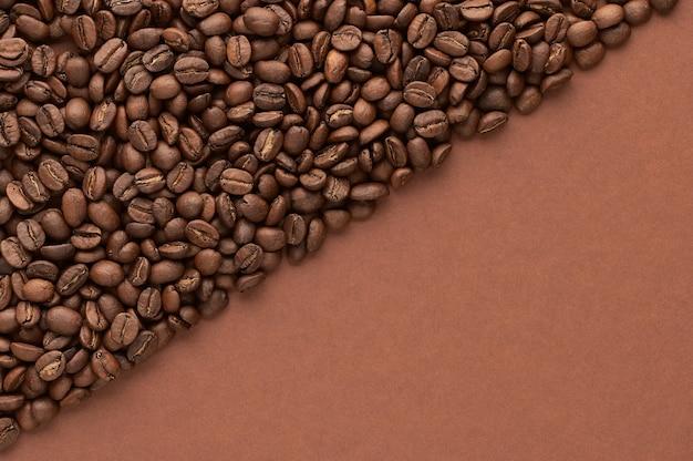 Gebrande koffiebonen op bruine achtergrond met kopie ruimte. close-up bovenaanzicht.