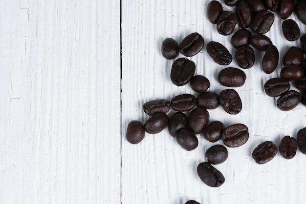 Gebrande koffiebonen op witte houten lijst. koffie achtergrond met kopie ruimte.