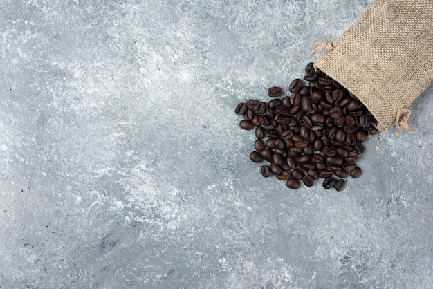 Gebrande koffiebonen uit jutezak op marmer.