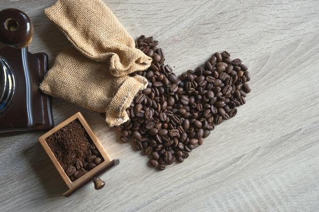 Gebrande koffiebonen uit zak in de vorm van het symboolhart op rustieke houten achtergrond. Premium Foto