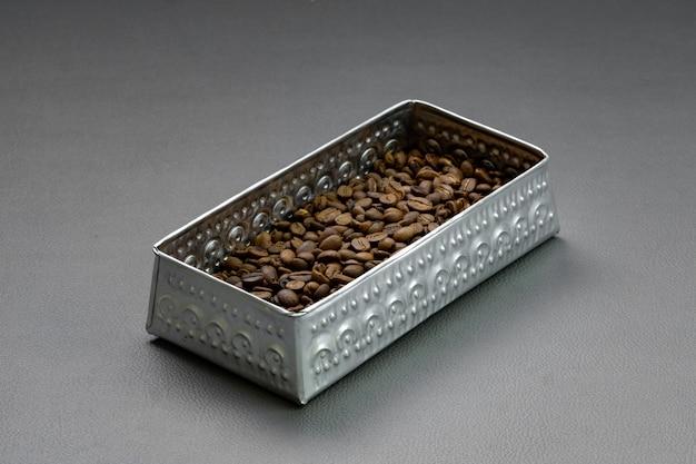 Gebrande koffiebonen worden in aluminium bakjes op een grijze ondergrond geplaatst.