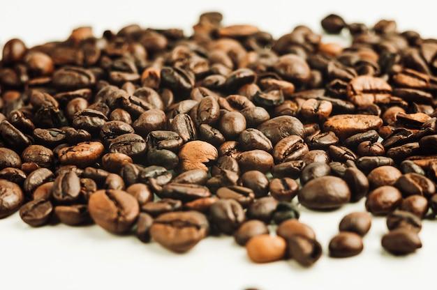 Gebrande koffiebonen zijn in stapel geïsoleerd op een witte achtergrond
