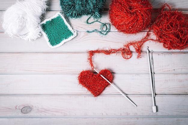 Gebreid hart handgemaakt op houten tafel, bovenaanzicht.
