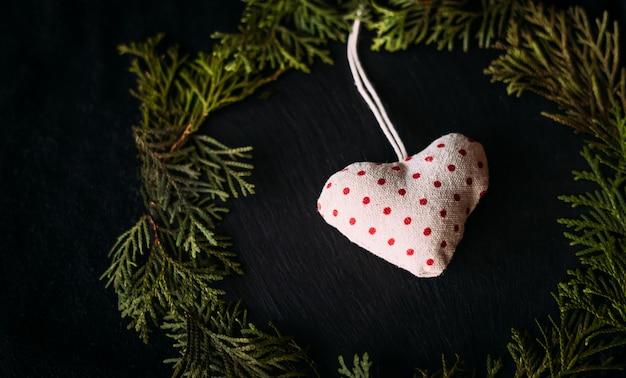 Gebreid hart met rode erwten ligt met kerstboomtakken.