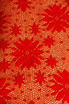 Gebreid kant. het materiaal wordt willekeurig op een horizontaal oppervlak gevouwen. monster van stof. rood kant