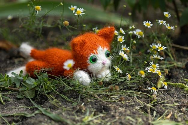 Gebreid speelgoedkatje, gemberkatje met bloemen in de natuur