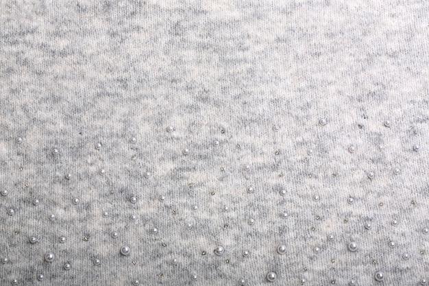 Gebreide achtergrond. lichtgrijs zacht wolpatroon als achtergrond. achtergrond geborduurd met kralen