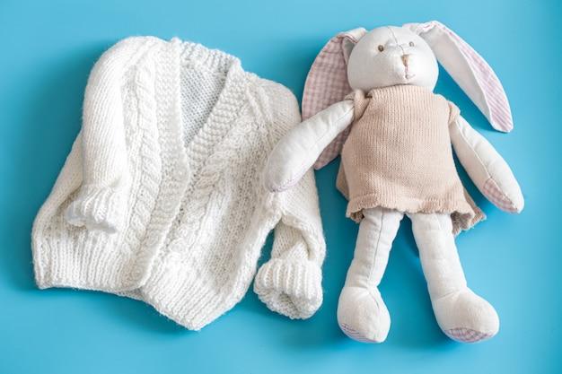 Gebreide babykleding en accessoires op een blauwe achtergrond.