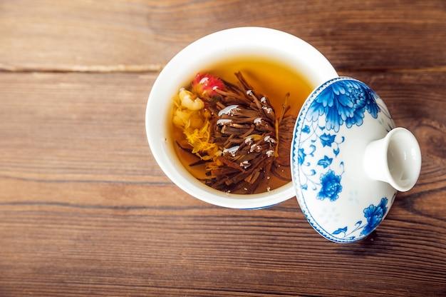 Gebreide bloeiende thee in een porseleintheepotclose-up.