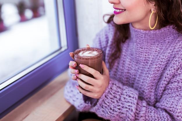 Gebreide dikke trui. glimlachend positief meisje met gele oorbellen en paarse lippenstift die cacao houdt en uit het raam kijkt