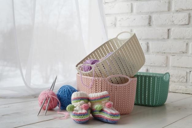 Gebreide dingen en handwerkaccessoires in huismanden, gekleurde manden