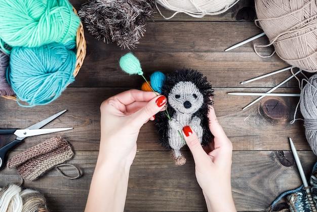 Gebreide egel met ballonnen geschenken handgemaakt breien op houten achtergrond gebreid speelgoed maken