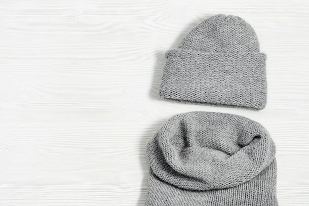 Gebreide grijze muts en sjaal op witte houten achtergrond. modieuze warme kleding voor meisje of vrouw. plat leggen. bovenaanzicht kopieer ruimte.