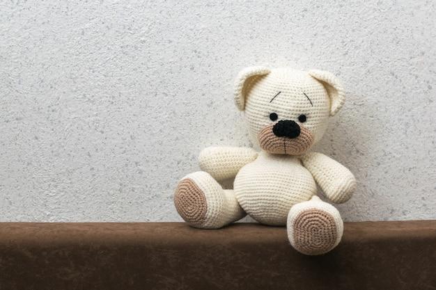 Gebreide ijsbeer met bruine pootjes op de bank tegen de muur. mooi gebreid speelgoed.