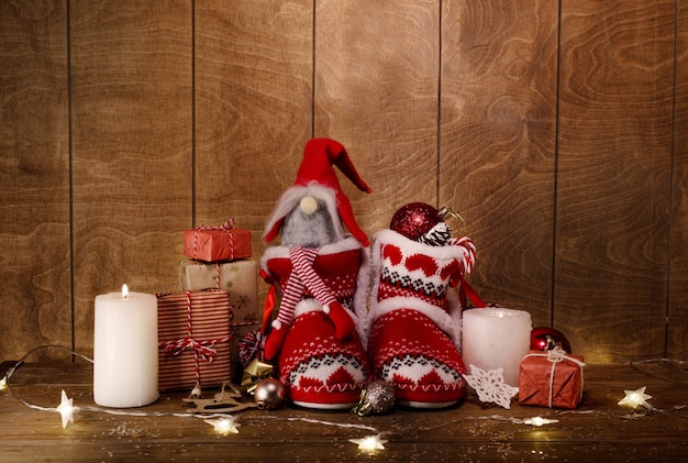 Gebreide kerstlaarzen op een houten achtergrond rond geschenken, kaarsen branden lichten