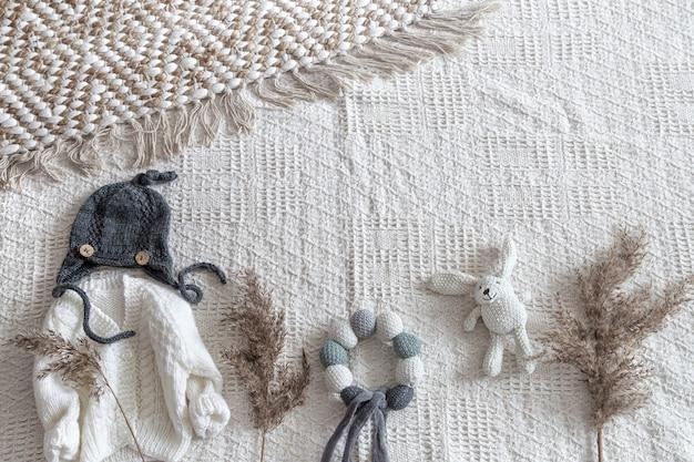 Gebreide kinderkleding op een lichte achtergrond met accessoires.
