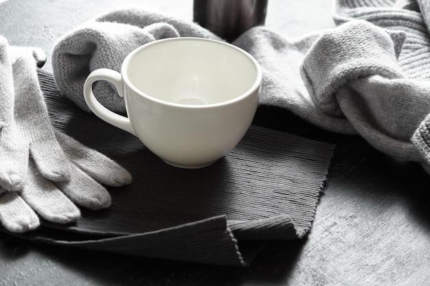 Gebreide kleding en koffiemokken op zwarte ondergrond
