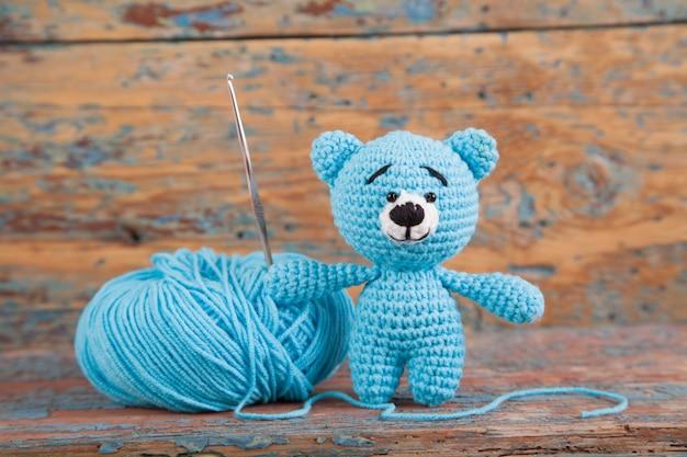 Gebreide kleine beer op een oude houten achtergrond. handgemaakt, gebreid speeltje. amigurumi