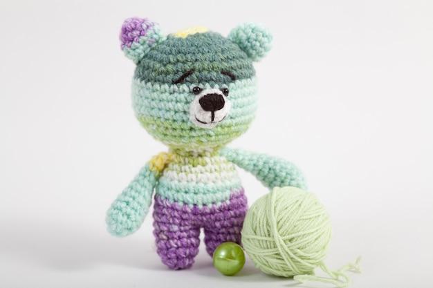 Gebreide kleine beer op een witte achtergrond. handgemaakt, gebreid speeltje. amigurumi