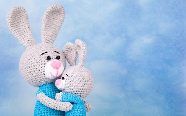 Gebreide konijnen - moeder en zoon met geschenken en bloemen. gebreid speelgoed, handgemaakt, amigurumi, creativiteit, doe-het-zelf. moederdag kaart