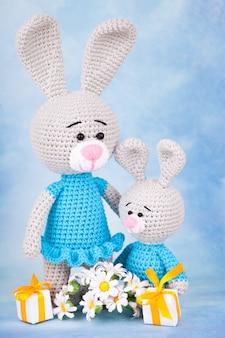 Gebreide konijnen - moeder en zoon met geschenken en bloemen.