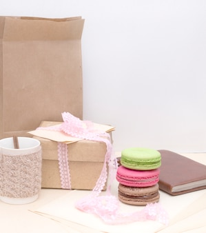 Gebreide mok en kleurrijke bitterkoekjes op ruwe papieren zak