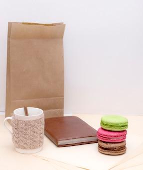 Gebreide mok, kleurrijke bitterkoekjes en kladblok op papieren zak