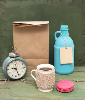 Gebreide mok, macaroon, blauwe fles, klok en ruwe papieren zak