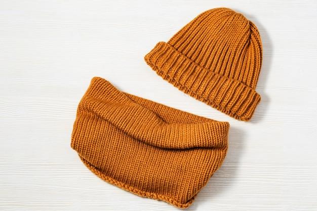 Gebreide oranje hoed en sjaal op witte houten achtergrond. modieuze warme kleding voor meisje of vrouw. plat leggen. bovenaanzicht kopieer ruimte.