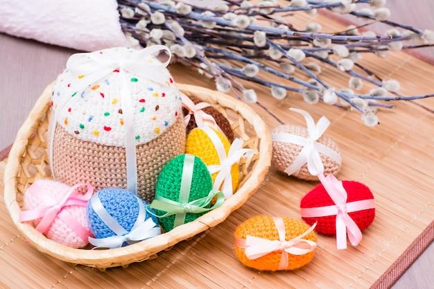 Gebreide paaseieren en pasen-cake in een rieten mand op een houten lijst