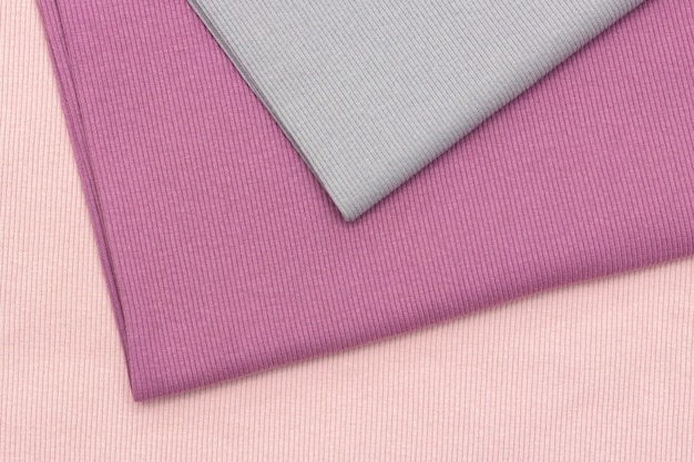 Gebreide stof textuur. drie lappen stof van verschillende kleuren liggen op elkaar. mooie achtergrond. pastelkleuren, roze, grijs.