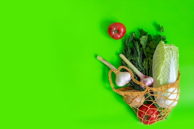 Gebreide tas op een groene tafel met groenten: tomaten, knoflook, aardappelen, kool, uien en een bosje dille.