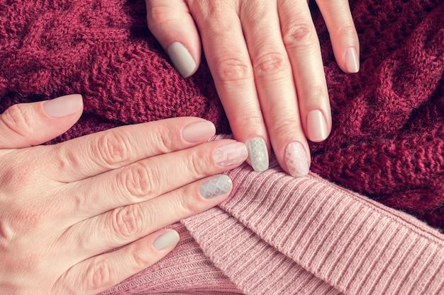 Gebreide textuurmanicure op nagels van roze en grijze kleuren