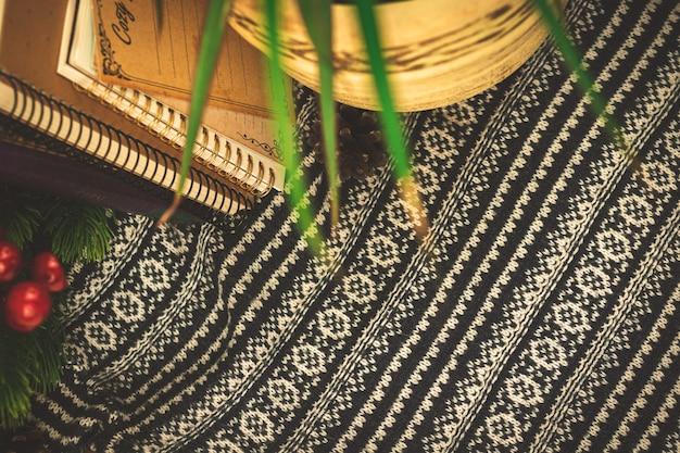 Gebreide trui achtergrond met boeken homeplant en andere winterdecoratie, kopieer ruimte. hoge kwaliteit foto