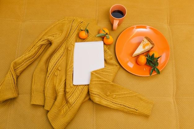 Gebreide trui, kopje koffie, cheesecake, mandarijnen, notitieboekje op oranje tafel