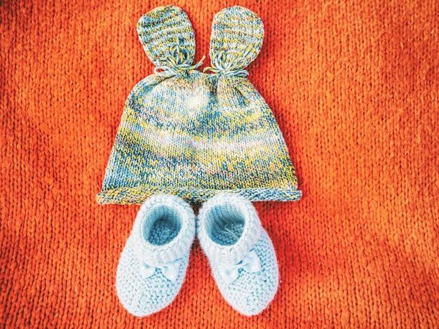 Gebreide veelkleurige hoed in de vorm van konijnenoren en blauwe wollen slofjes voor een pasgeboren baby op een rode gebreide wollen ondergrond, het concept van wachten op het eerste kind in het gezin