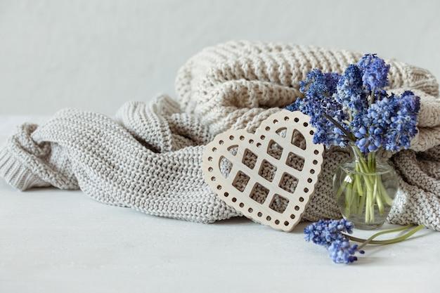 Gebreide warme truien in pastelkleuren, een boeket muscari bloemen en een decoratief houten hart.