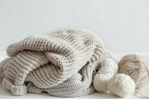 Gebreide warme truien in pastelkleuren en strengen draad close-up.