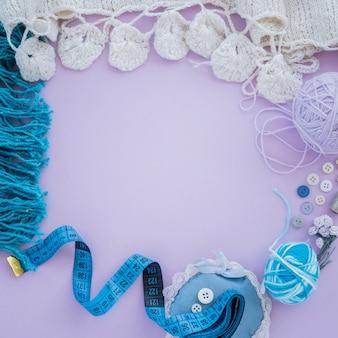Gebreide witte sjaal met wol; knop; meetlint op paarse achtergrond