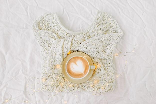 Gebreide witte trui en kopje koffie op witte achtergrond. winter mode-concept. bovenaanzicht plat lag.